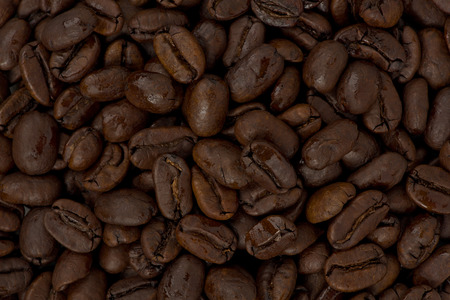 Background texture of whole dark roasted coffee beans.