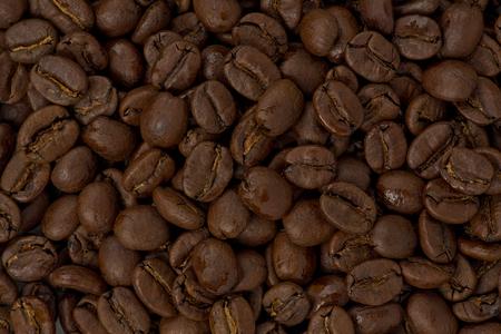 Background texture of whole medium-dark roasted coffee beans. Stok Fotoğraf