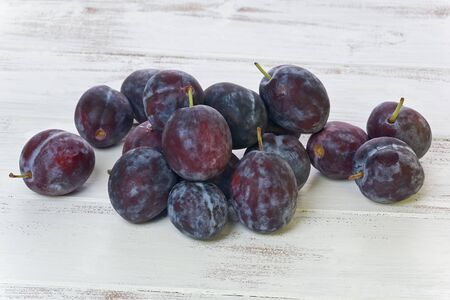 Several whole Prune plums, or Empress plums, on a painted white background.