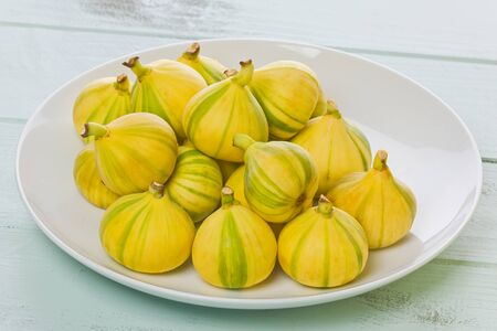 White plate with several whole Tiger striped figs, also known as Panache figs, and Candy striped figs on a painted background.