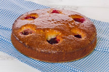 Almond Plum Cake on a blue checkered cloth on painted white background.