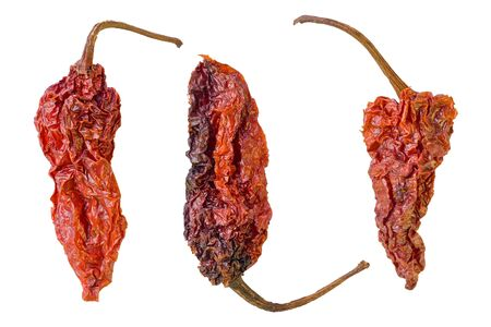 Three dried Ghost peppers against a white background.