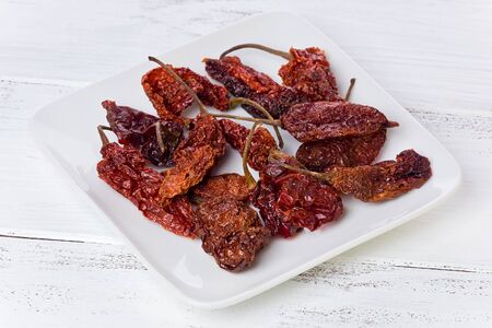 A small plate of dried Ghost chile peppers on a painted white background.