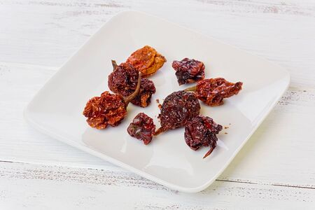 Several dried Scorpion chile peppers on small white plate, on a white painted background.