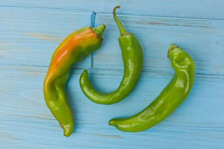 Three fresh, whole, Hatch chile peppers on a painted blue background.