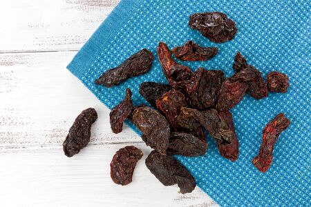 Several dried Morita chile peppers on a blue cloth, resting on a painted white background. Stok Fotoğraf