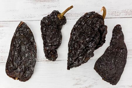 Four dried Poblano chile peppers on a painted white background.