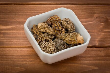 Several dried Morel, or Morchella mushrooms, in a small white bowl on a wood background.