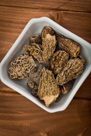 Several dried Morel mushrooms in a small white bowl on a wood background.
