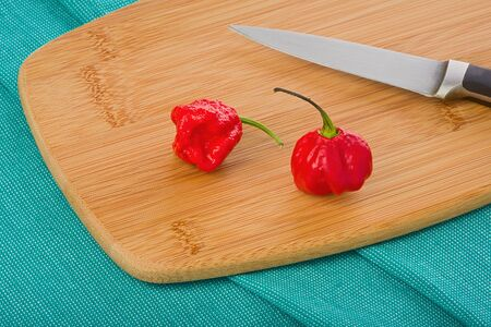Two whole, raw, 7-Pot chile peppers on a wooden cutting board with knife on a green cloth.