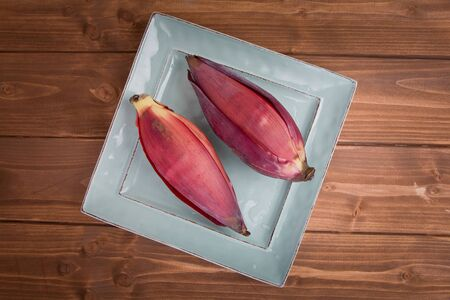 Two Banana blossoms, or banana hearts, on a small square plate on a wood background.