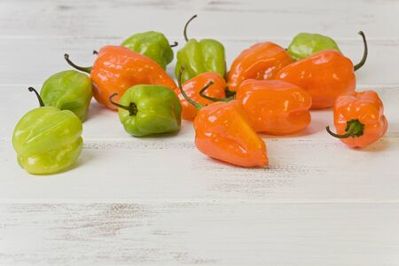 Several whole orange and green chile Habanero peppers on a painted white background.