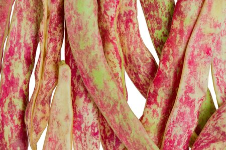 Background texture of several raw, whole, Cranberry beans, also known as Borlotti, against a white background.