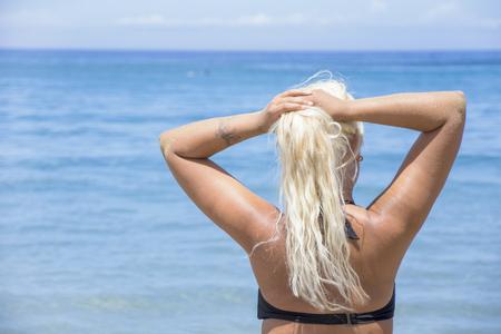 금발의 여인은 그녀의 휴일 동안 해변에서 휴식을 취하기로 결정합니다. 스톡 콘텐츠