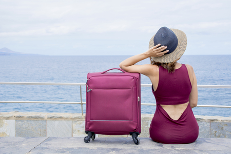 The young woman seated with her suitcase, thinks about her next travel.