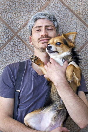 Portrait of a man with his dog lying on the ground.