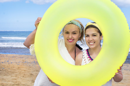 Young women with a donut-shaped float on the beach. Banco de Imagens