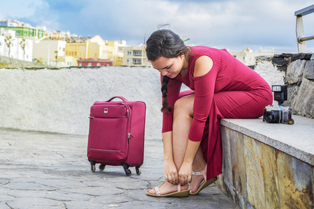 Young woman with luggage and photo camera, sitting outdoors, she buckles her sandals, to start her vacations.