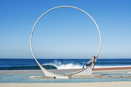 Man leaning on a circular sculpture facing the sea.
