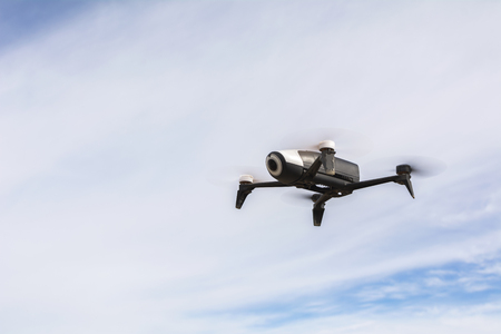 Drone black and white, with video camera, hanging in the air, with blue sky with clouds in the background.