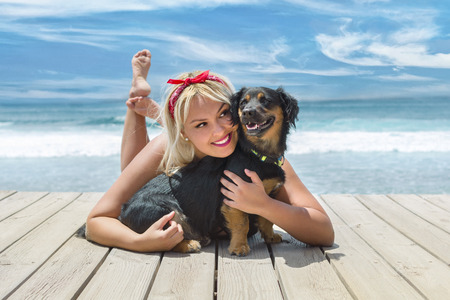Young, blonde, hugging her very happy dog, near the beach, with the blue sea behind.