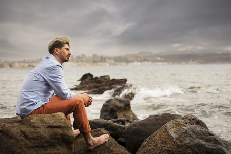 Man sitting on the rocks of the coast near the sea, barefoot and melancholy. Stormy day.