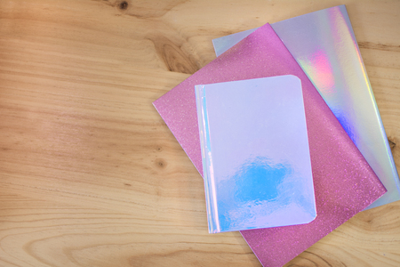 Colored notebooks iridescents with glitter on wooden desk for the return to school. Stock fotó