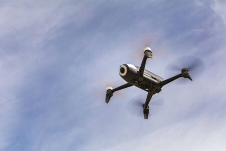 aerial shot, from below, of a drone robot isolated on the blue sky background