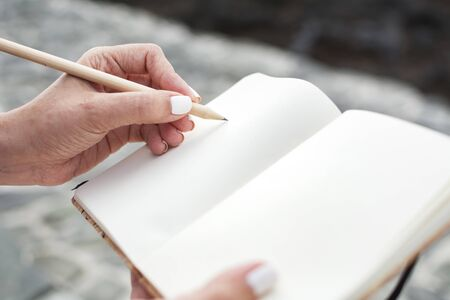 Close-up of a woman's hands writing in her notebook with a wooden pencil. Outdoor.