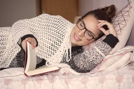woman with glasses that read a book lying on the bed and wrapped with blanket in the cold winter ..