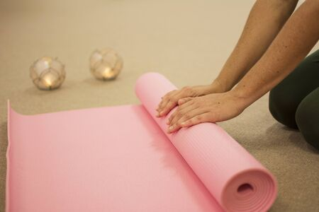 Womans hands rolling up a pink yoga mat.