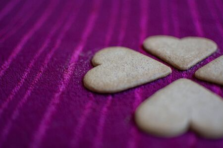 Heart-shaped cookies that in turn, together, make the shape of a four-leaf clover, isolated on a red background.