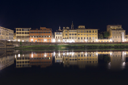 Night shot of typical houses of Florence with its reflection on the river Arno