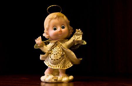 Figurina representing a little angel holding a glim wearing a little golden dress photo