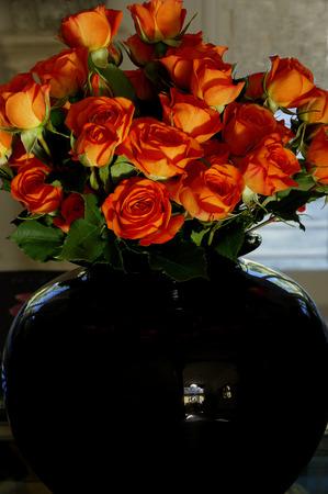 rosas naranjas: Rosas anaranjadas miniatura en florero negro Foto de archivo