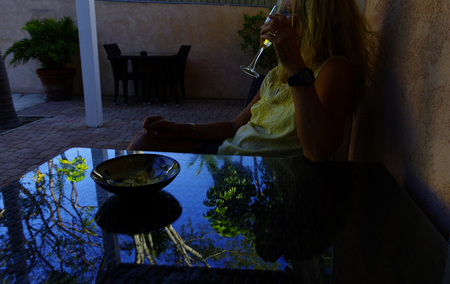 Glass of wine by the pool at dusk.