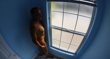 aqua naked: Nude man contemplates by the window