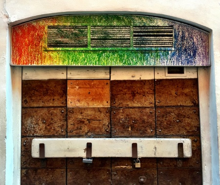 loopholes: Closed wood door with loopholes painted with colors on top