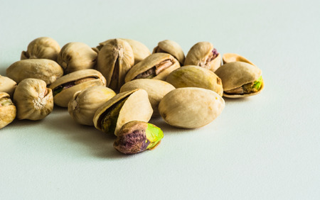 split up: a group of pistachios, one is without its shell