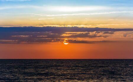colores calidos: hermoso amanecer del final del verano con colores cálidos y mar en calma oscura