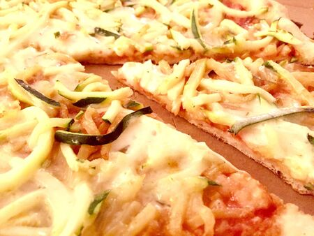 aereal: Aereal view of a slice of pizza with zucchini and potatoes cut  in thin slices in a cardoard box