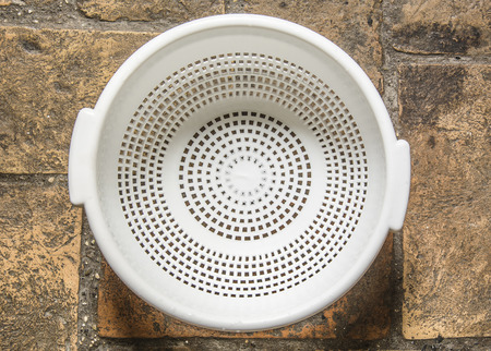 a colander: white colander for pasta on a rough bricked floor