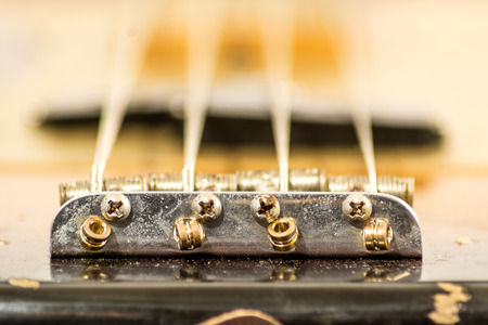 g string: close up of a bridge in the body of an electric bass