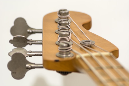 the head of a four strings electric bass with its prockets, string guide, palette and tuners Stock Photo