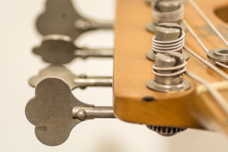 close up of tuning heads of a electric bass