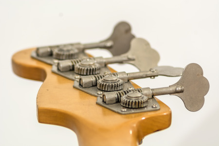 Rear view of a electric bass head with gears, screws and tuners Stock Photo
