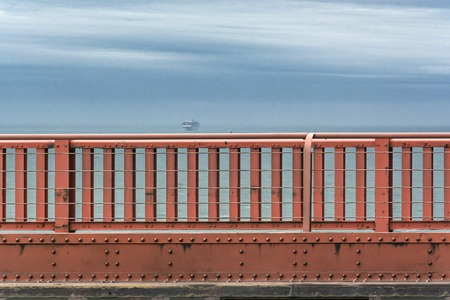 Golden Gate Bridge parapet with a ship on the background