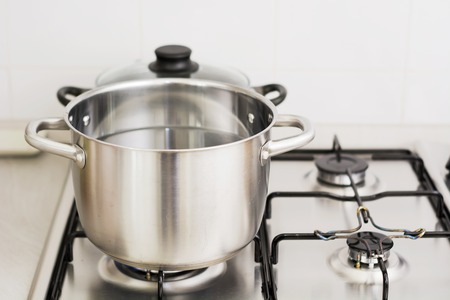 upscale: Close-up of stainless steel cooking pot on gas stove in contemporary upscale modern home kitchen. Selective focus on pot. Stock Photo