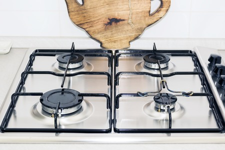 domestic kitchen: stove top of a domestic kitchen with a wooden plate