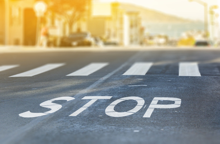 City crosswalk with symbol stop, closeup road texture with blurred San Francisco Bay in background in a warm sunny day